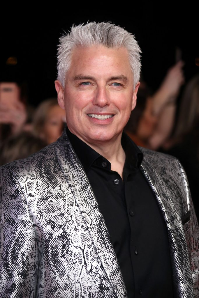 John Borrowman stands in front of a blurred black background with people in it wearing a black button-up shirt and a silver and black metallic snake print suit jacket.