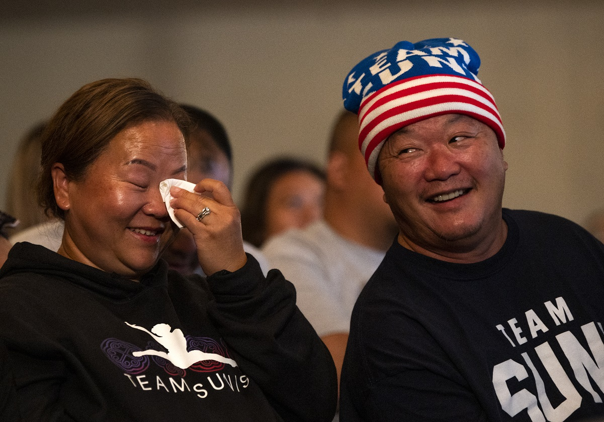 John Lee and Yeev Thoj reacting to their daughter competing on the balance beam