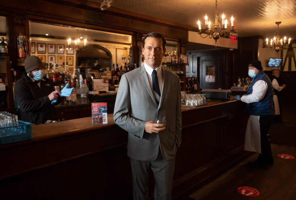 Madame Tussauds' Jon Hamm wax figure holds a glass of whiskey by the bar at Peter Luger Steak House in New York City in February 2021
