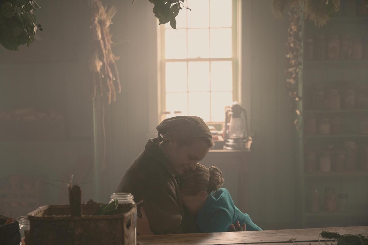 Elisabeth Moss as June and Mckenna Grace as Esther in 'The Handmaid's Tale' Season 4. June wears a beige Martha uniform as she hugs Esther, who wears a teal Wife dress.