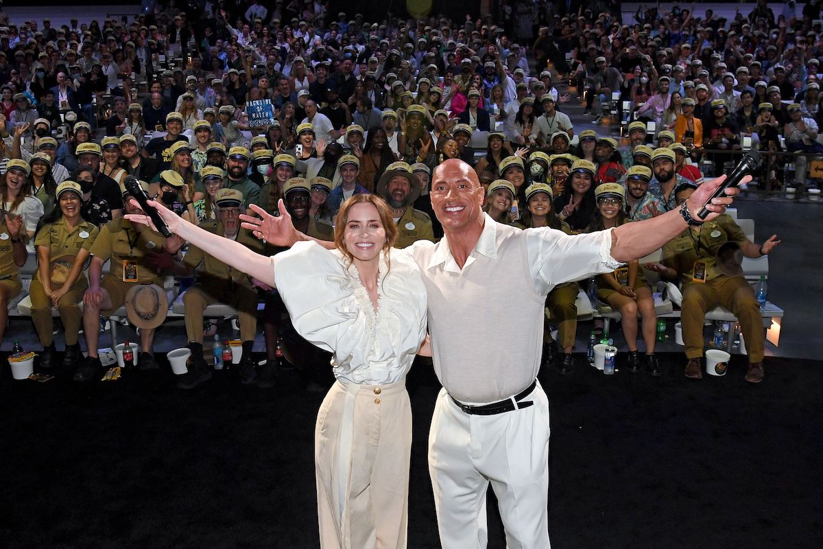 Emily Blunt and Dwayne Johnson pose onstage with their arms wide open