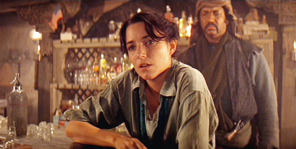 Karen Allen as Marion Ravenwood sitting in a bar with a fire behind her in 'Indiana Jones and the Raiders of the Lost Ark'
