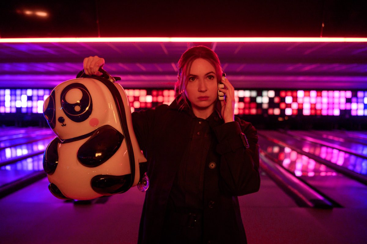 Karen Gillan as Sam in Gunpowder Milkshake. She's holding up a backpack and standing in a bowling alley.