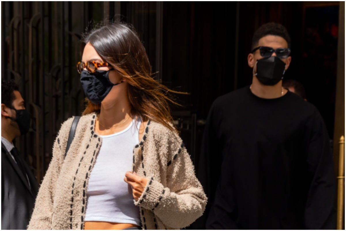Kendall Jenner and Devin Booker standing outside while wearing masks.