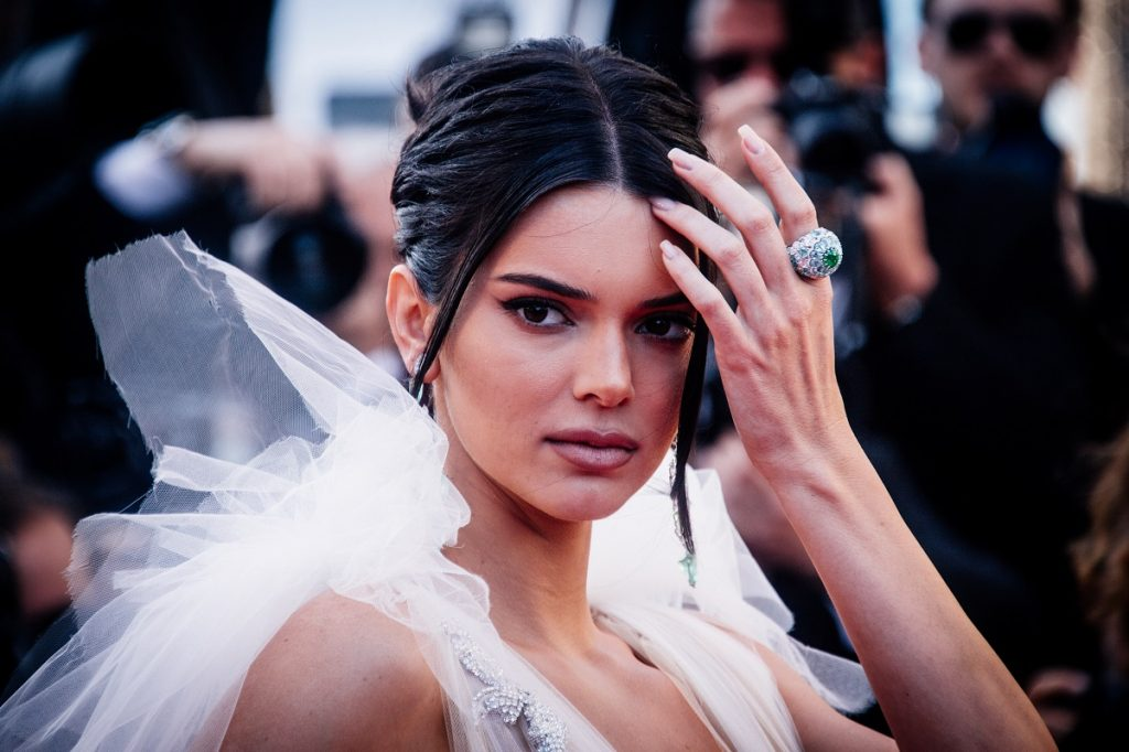 Kendall Jenner wearing a white ensemble with her hair pulled back at the Cannes Film Festival in 2018