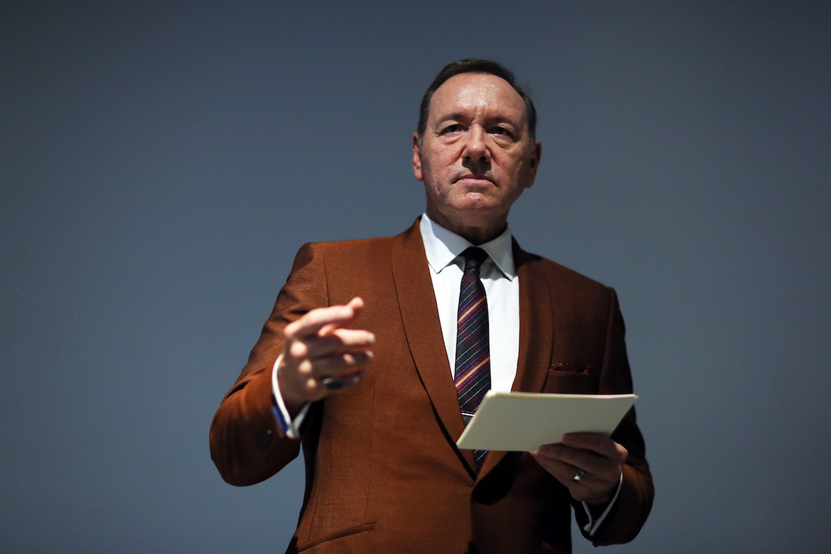 Kevin Spacey holding a piece of paper and pointing