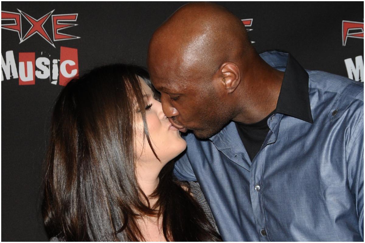 Khloé Kardashian and Lamar Odom kissing at an event.
