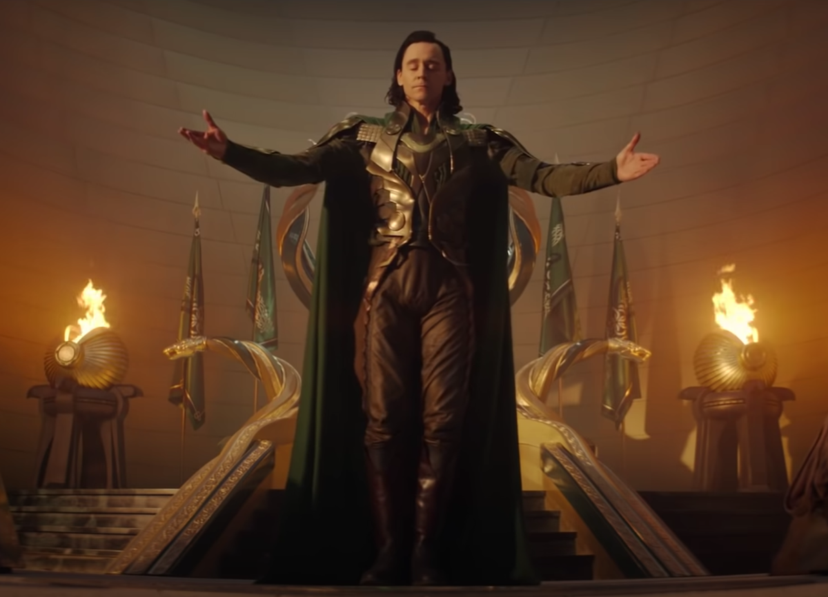 Tom Hiddleston in 'Loki.' He stands in front of a gold throne in what resembles Asgard. He wears a regal green cape and an armored green, gold, and black suit. His arms are outstretched as if accepting praise and his eyes are closed.