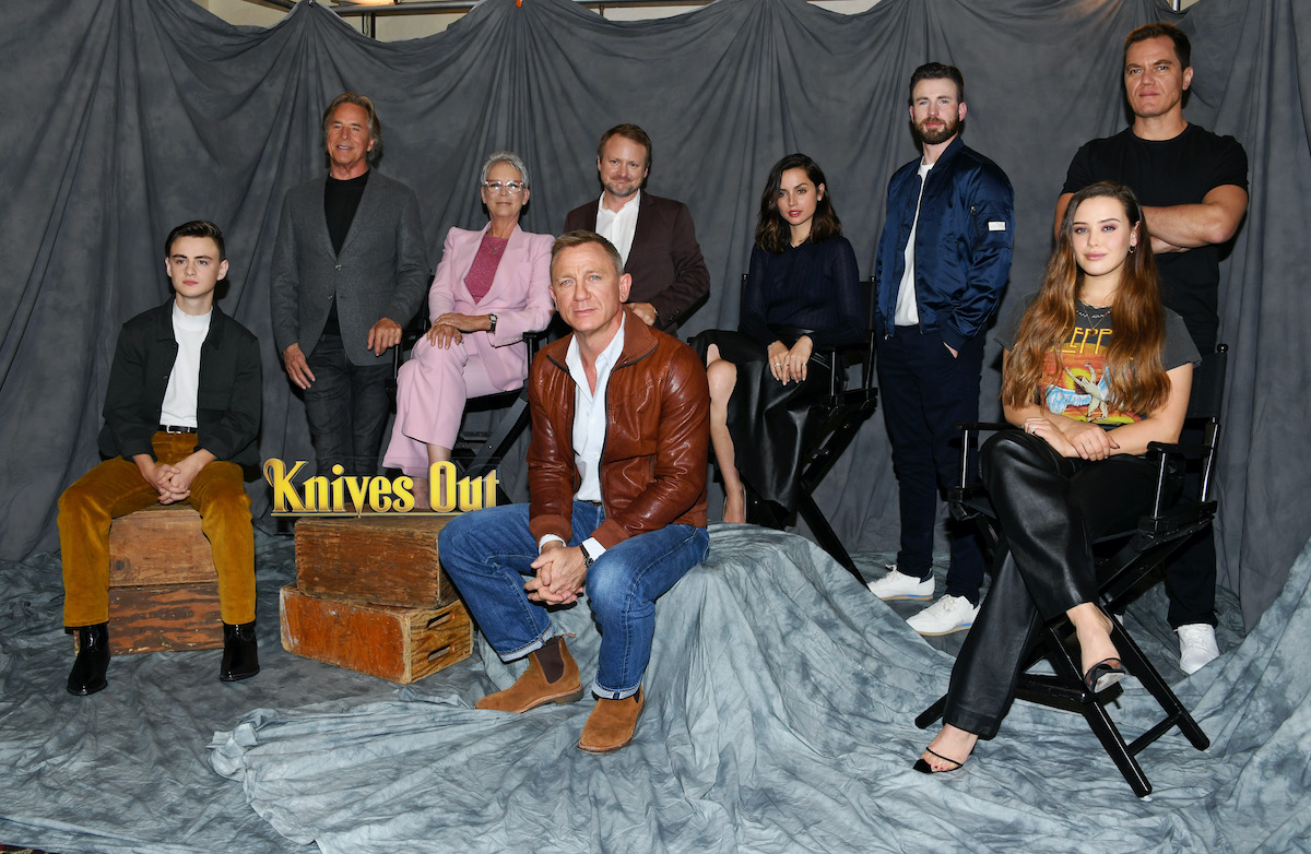 Daniel Craig and the rest of the 'Knives Out' cast pose next to the movie's logo