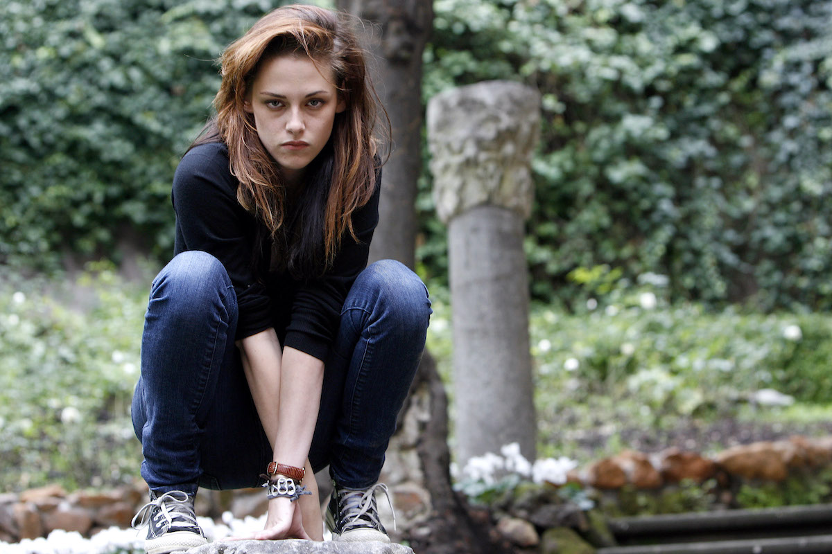 Kristen Stewart star of the Twilight movies crouches in character in blue jeans and a dark shirt