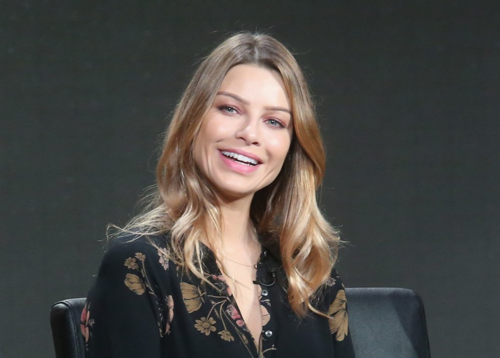 Lauren German laughing in front of a gray background