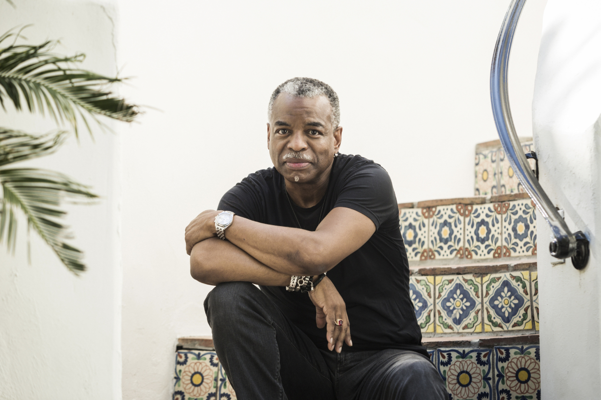 Actor LeVar Burton sits for a portrait in black pants and shirt with his arm crossed over his knee.