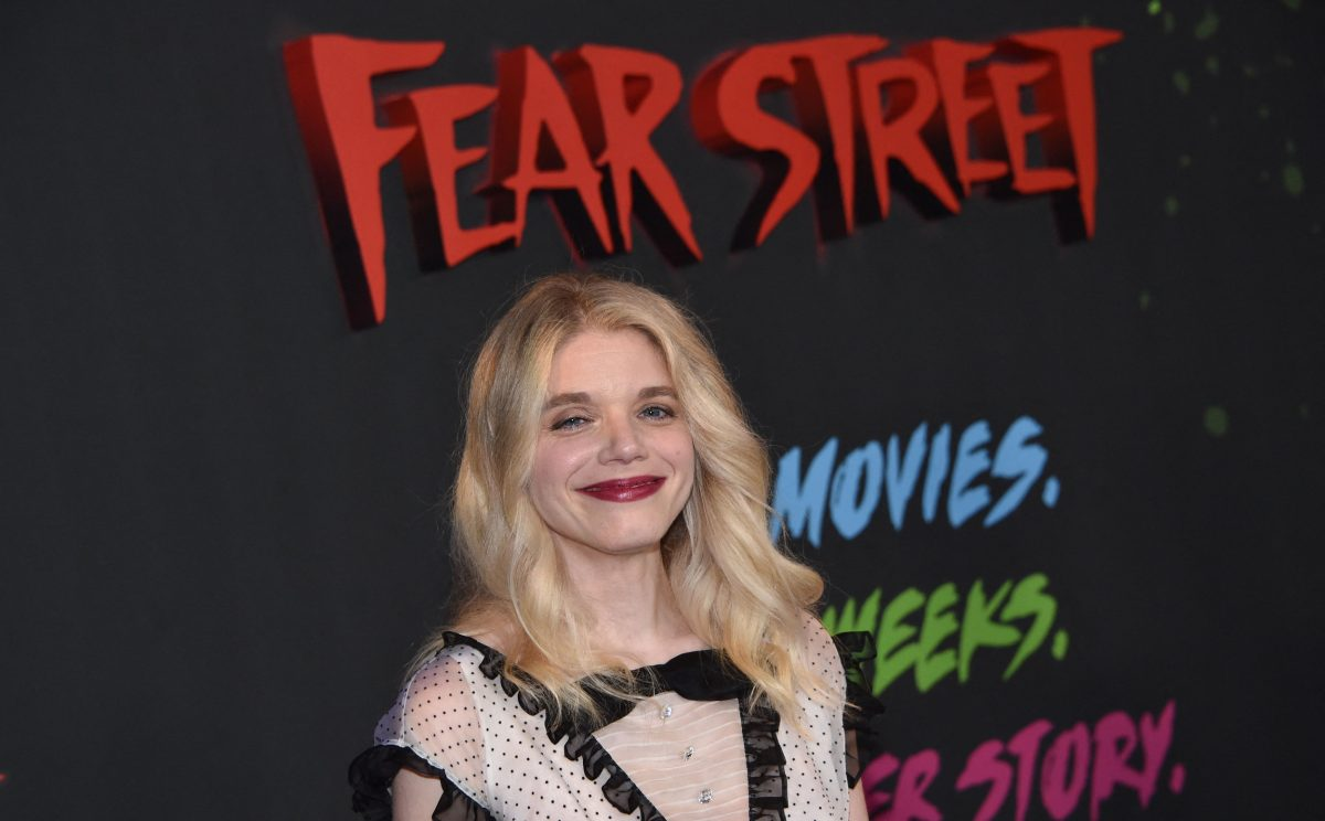 'Fear Street Part 2' director Leigh Janiak wearing an off-white and black dress in front of a Netflix wall