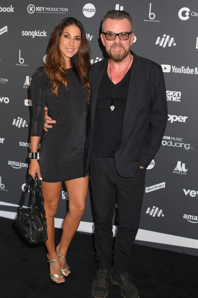 Leilani Dowding and Billy Duffy pose arm-in-arm on red carpet at Association of Independent Music Awards