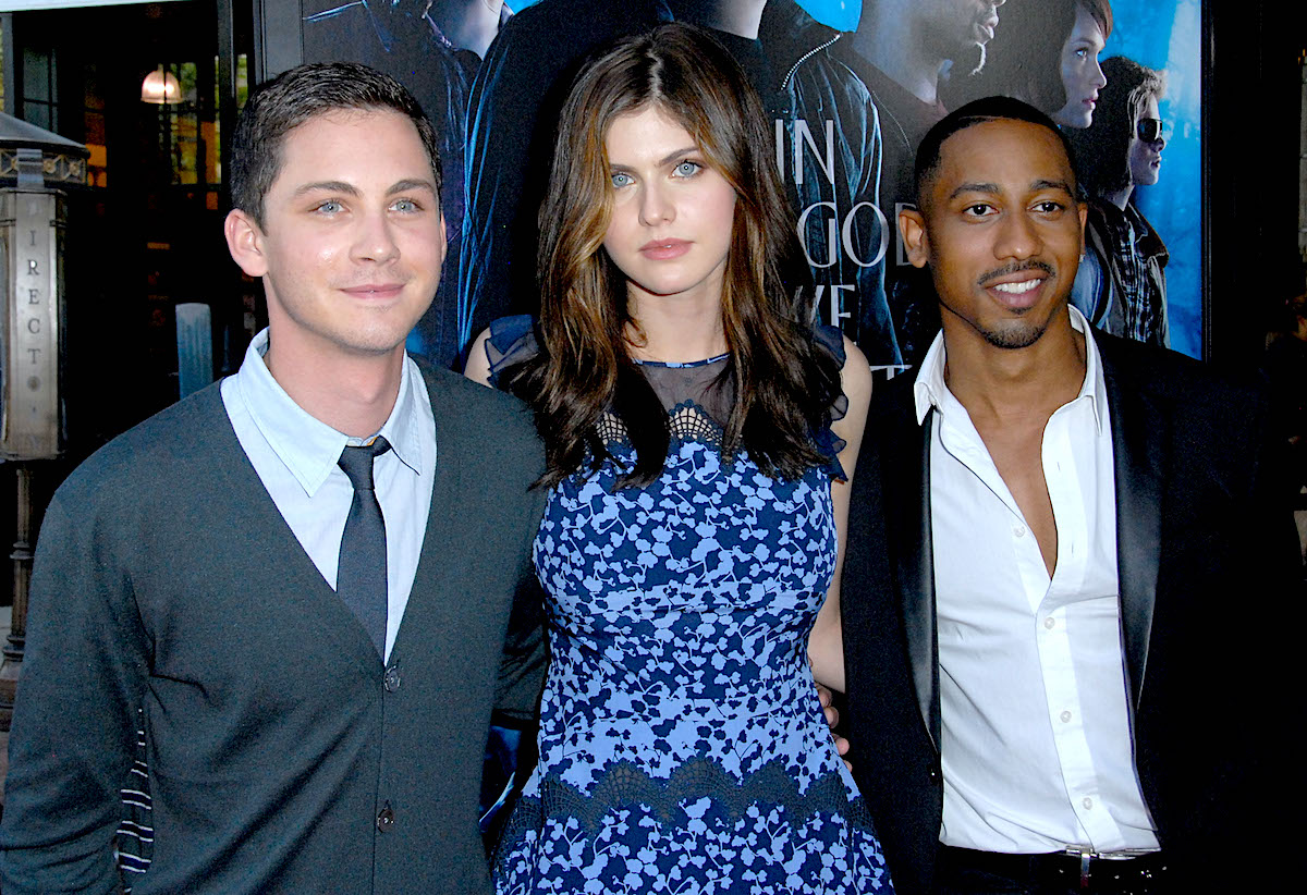 Logan Lerman, Alexandra Daddario, and Brandon T. Jackson at the premiere of 'Percy Jackson: Sea Of Monsters' in 2013. They stand side-by-side in front of a backdrop with the movie title on it.