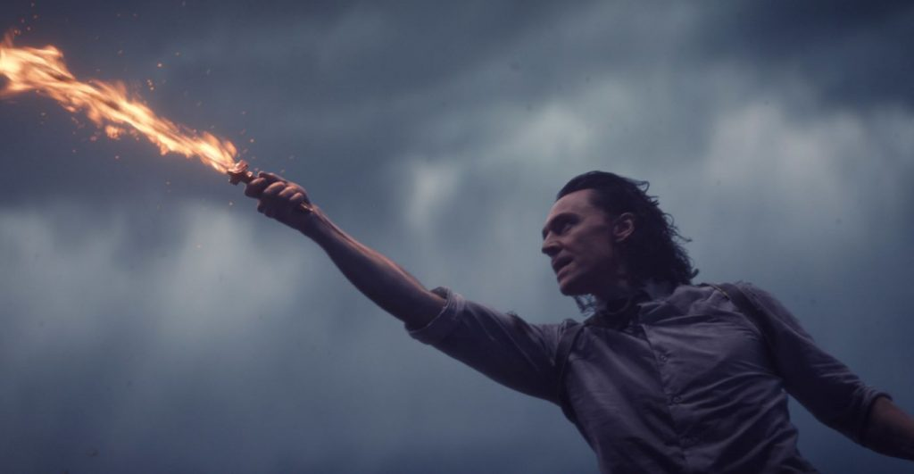 Loki wearing a white button up shirt with the sleeves rolled up with a flaming sword in his hand lunging to the side.