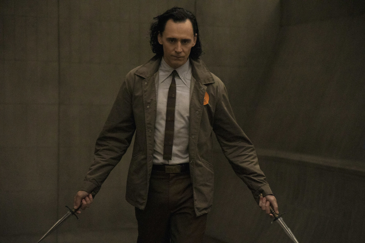 Tom Hiddleston holding a dagger in each hand in 'Loki' on Disney+. He wears a shirt and tie with a brown coat while walking down a brown hallway.