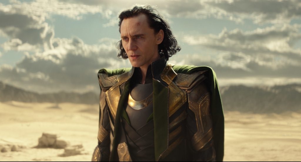 'Loki' star Tom Hiddleston standing in a desert landscape during the show's first episode