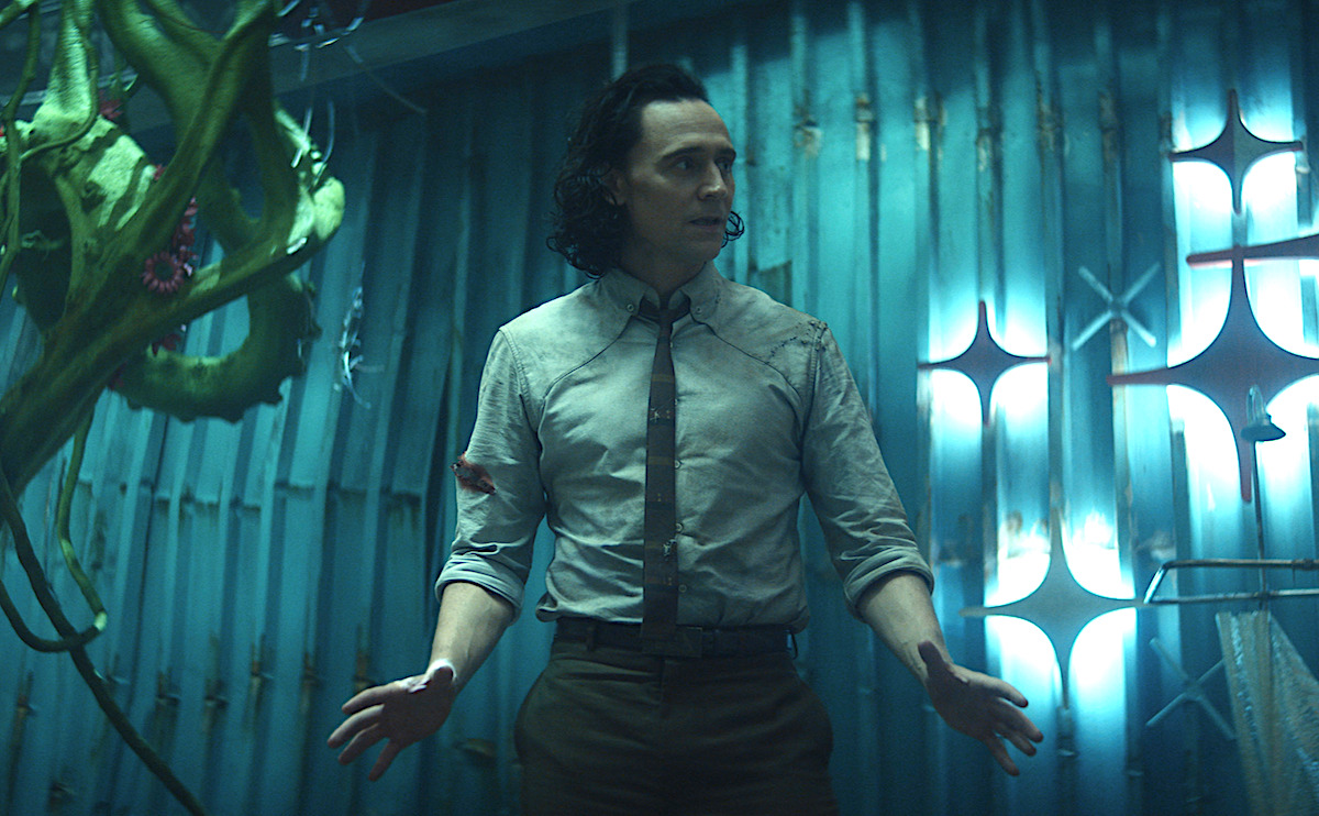 Tom Hiddleston in a shirt and tie in 'Loki' Episode 5 on Disney+. He stands looking concerned in an underground bunker built by other Lokis.