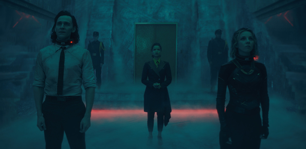 Tom Hiddleston, Sophia Di Martino, and Gugu Mbatha-Raw in 'Loki' Episode 4. Hiddleston wears a shirt and tie and Di Martino wears a black and green armored body suit. Both have electronic bands around their necks. Mbatha-Raw wears a brown and orange TVA uniform. They stand in a smoky room looking up at the Time-Keepers, off-camera.