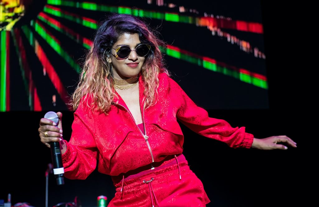 M.I.A smiling, holding a microphone on stage