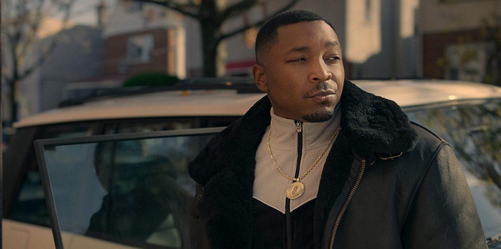 Malcolm Mays as Lou Lou standing outside of a car wearing a coat and chain in 'Power Book III: Raising Kanan'
