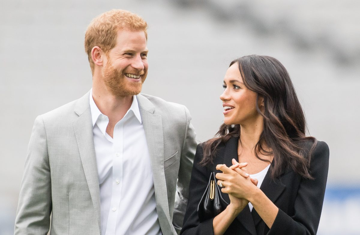 Meghan Markle smiling alongside her husband Prince Harry during a visit to the Gaelic Athletic Association