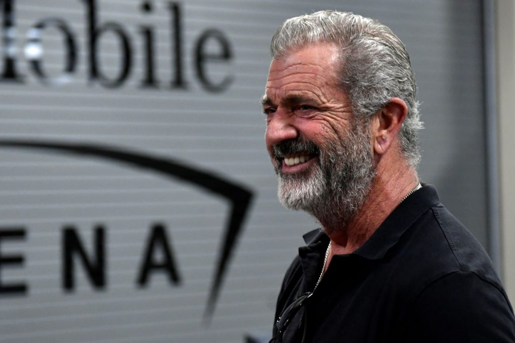 Mel Gibson stands in front of a rippled tin wall wearing a black polo.