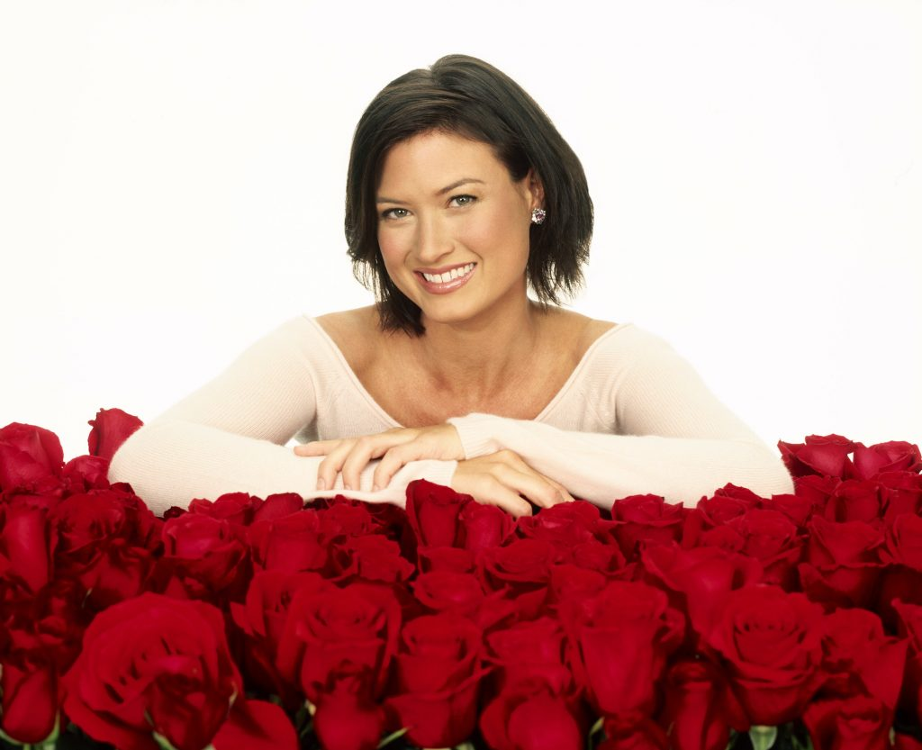 Meredith Phillips smiling, leaning over roses