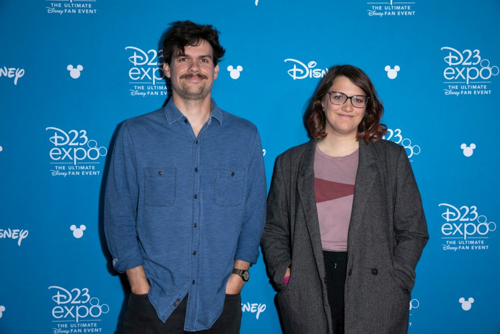 'Loki' writer Michael Waldron and director Kate Herron stand in front of a blue Disney wall
