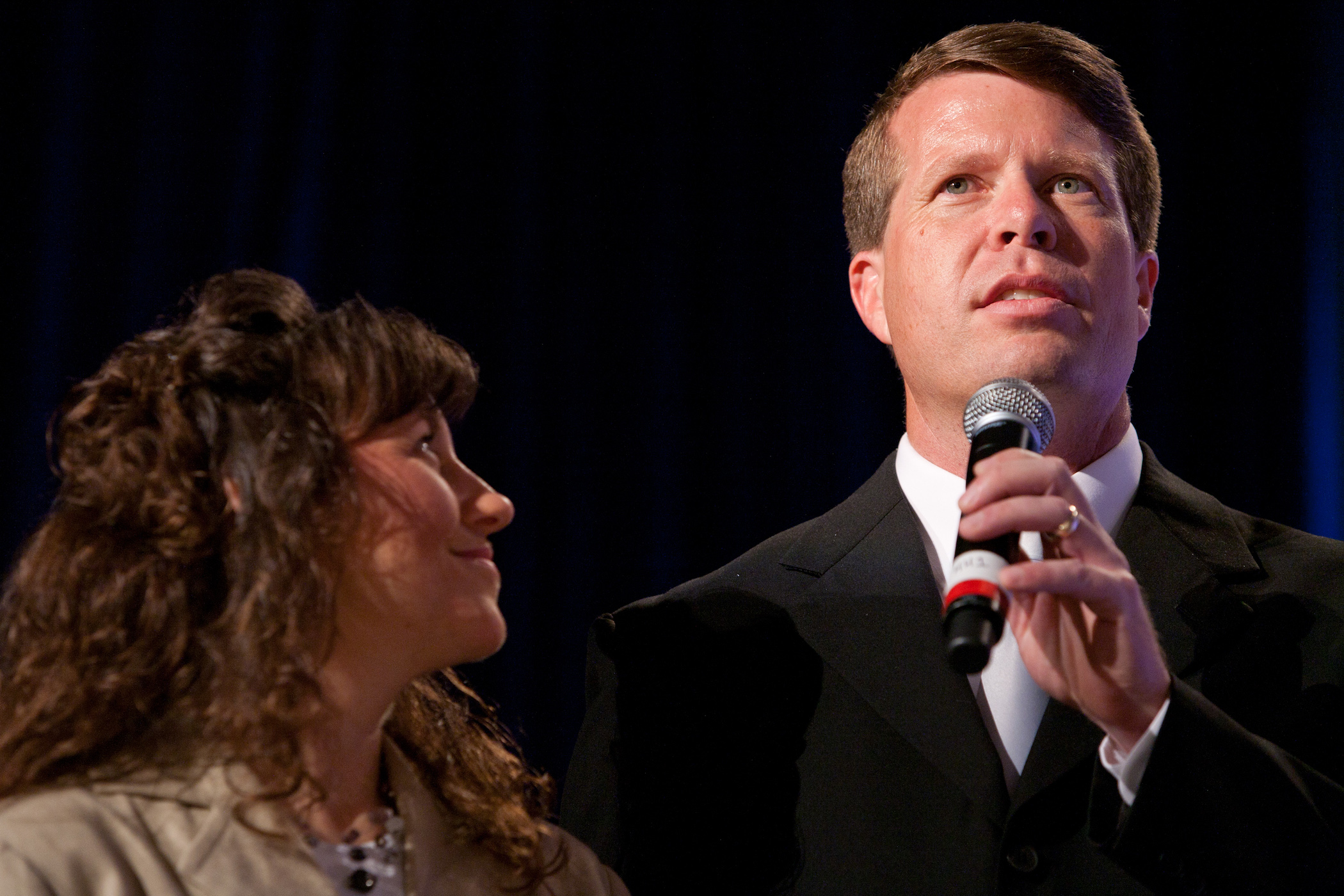 Michelle and Jim Bob Duggar from the Duggar family of TLC's 'Counting On' speaking at an event against a black background