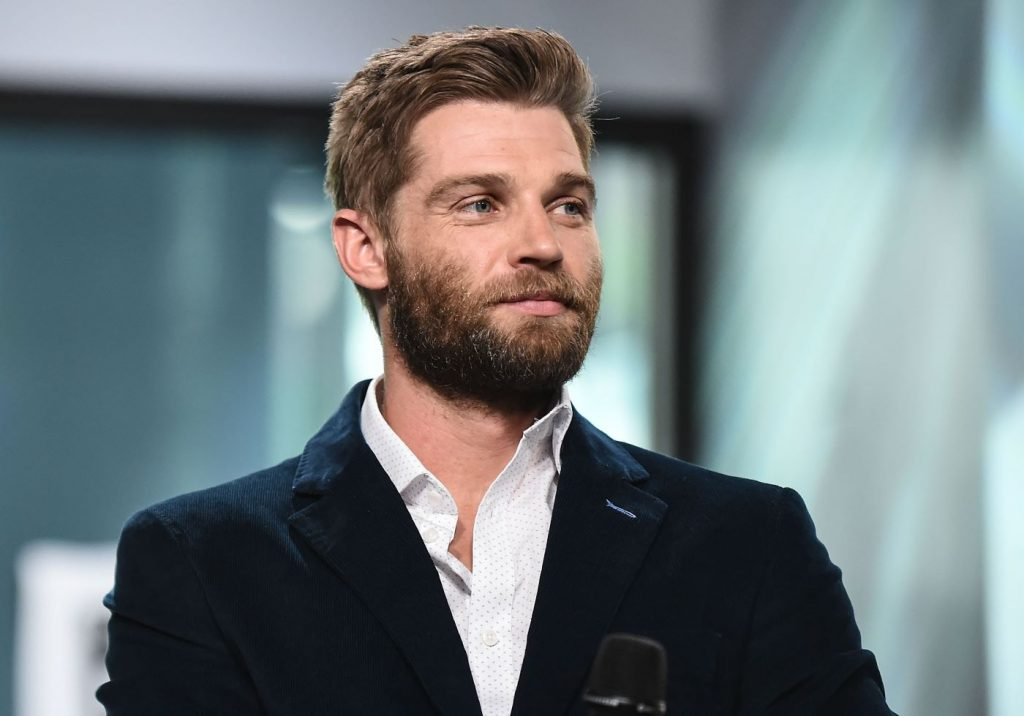 Mike Vogel dressed in a white shirt and a black jacket in front of a very blurred back ground of what looks like a window.