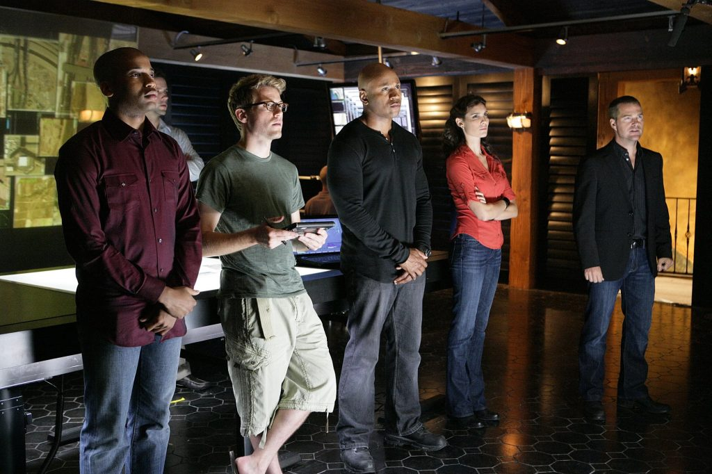 Chris O'Donnell (far right) stands next to the NCIS LA cast in the show's squad room.