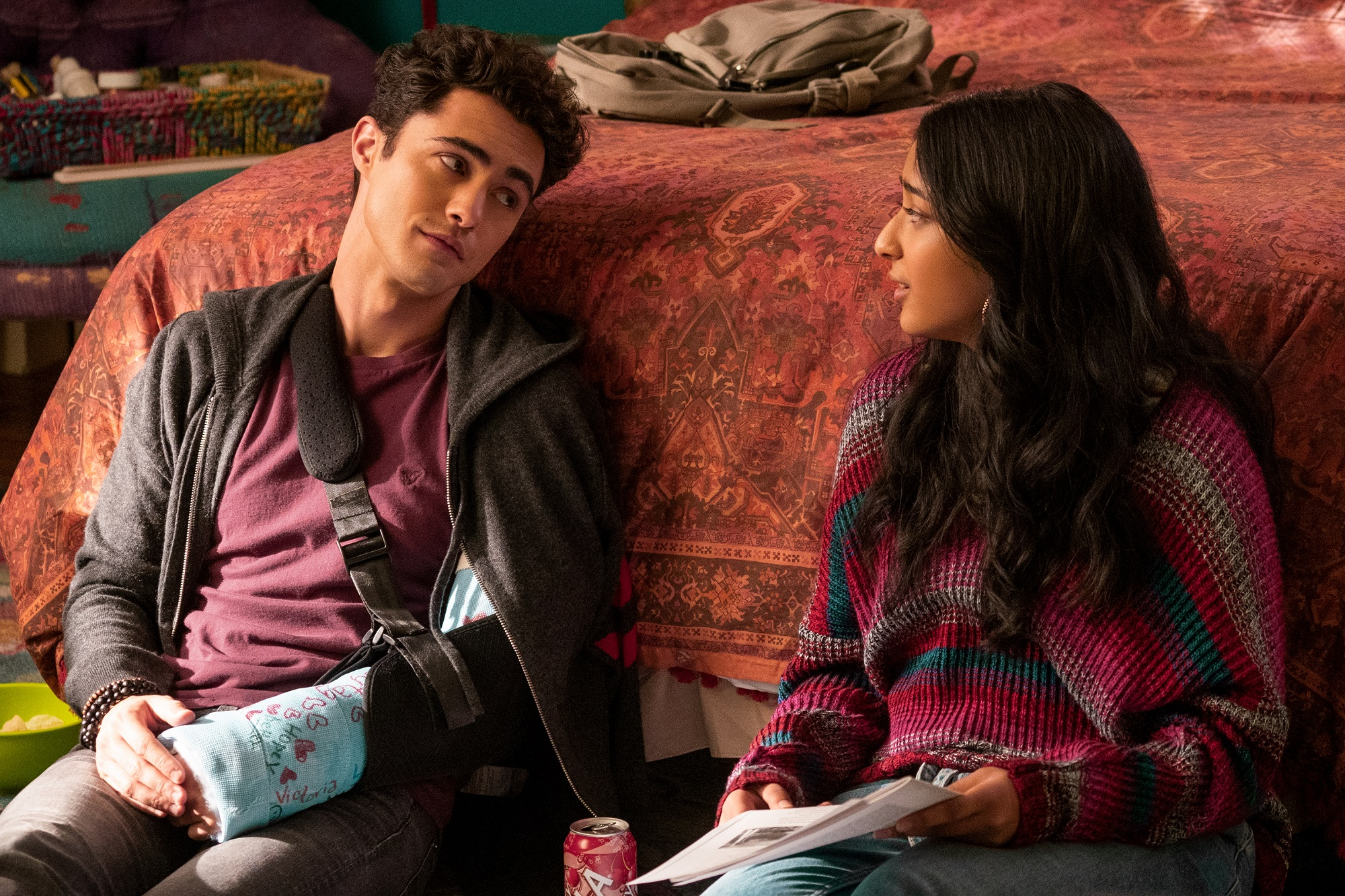 Paxton Hall-Yoshida and Devi Vishwakumar sit on the floor of Devi's bedroom in 'Never Have I Ever'