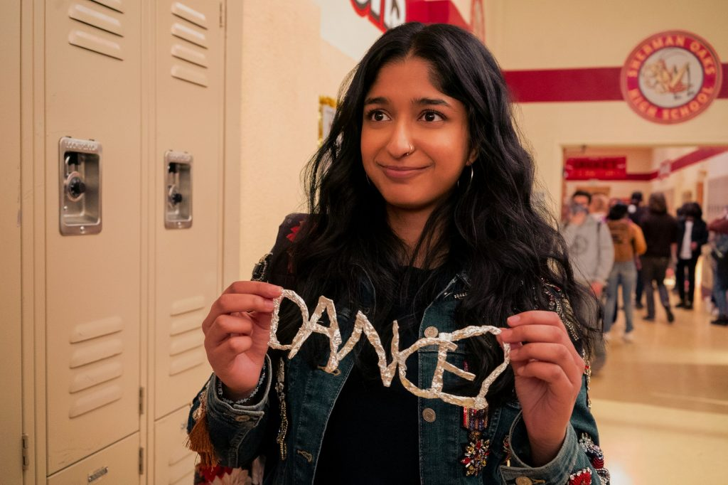 Devi holds up a homemade sign that spells 'Dance?' in 'Never Have I Ever'