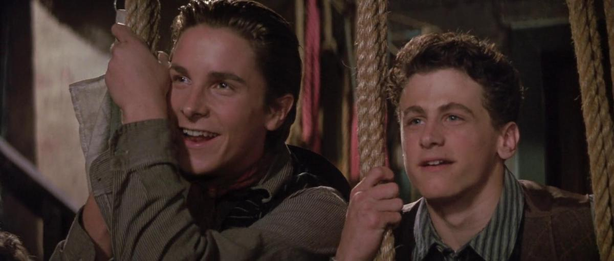 Christian Bale and David Moscow smile holding ropes and look on in the Disney movie 'Newsies'