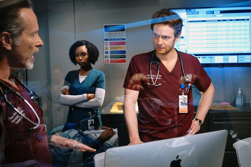 Dean Archer, Will Halstead and April Sexton talk in front of an Apple Computer during a scene on 'Chicago Med'