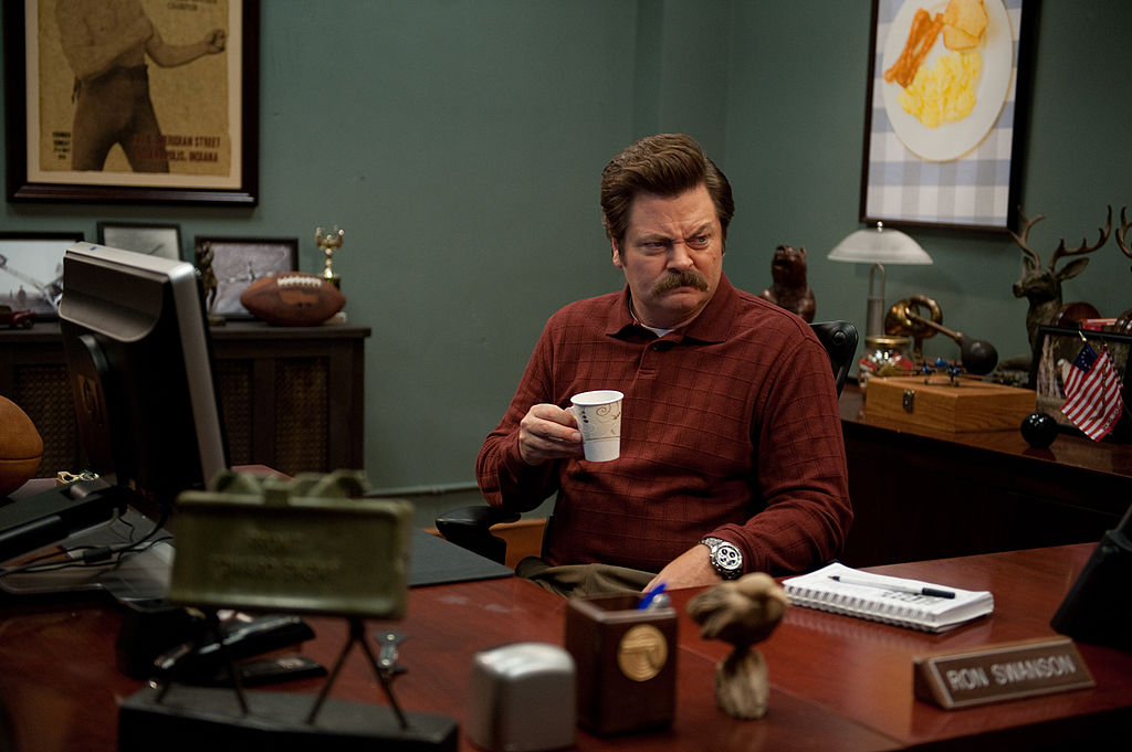 Nick Offerman as Ron Swanson drinks his coffee from behind his desk with a scowl on his face.