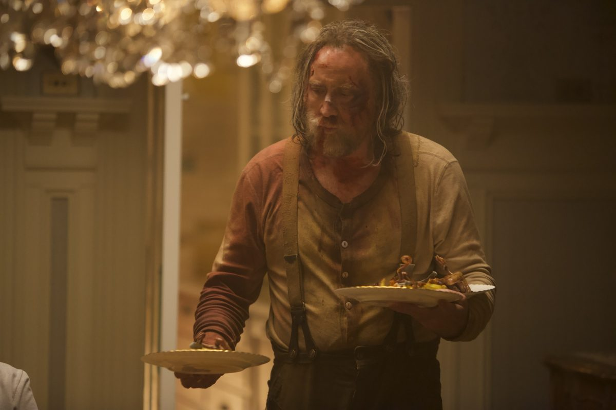 Nicolas Cage, bloodied after a fight, holds dinner plates