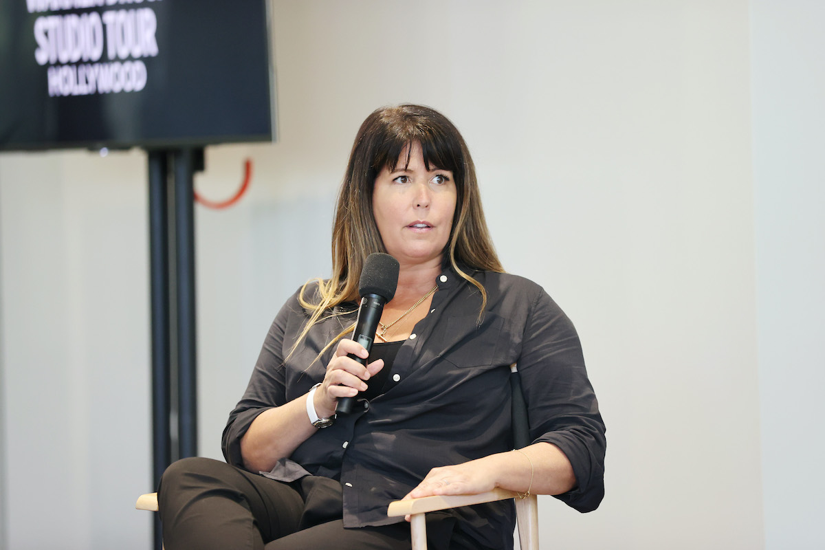 Patty Jenkins wears black and holds a microphone