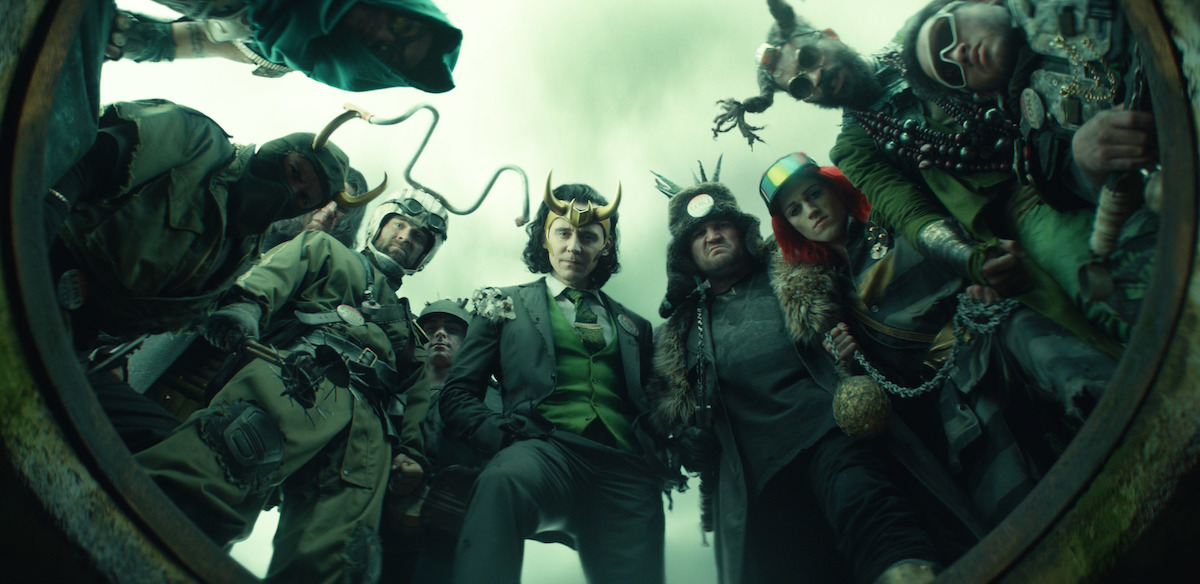 Tom Hiddleston as President Loki surrounded by other Lokis in 'Loki' Episode 5. The group looks down into the opening of an underground tunnel.
