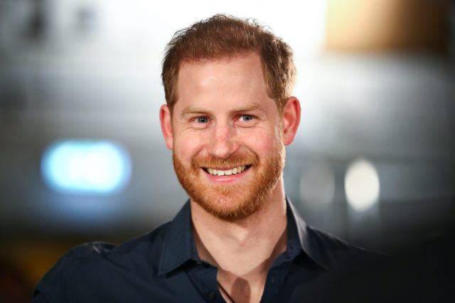 Prince Harry smiles in a black collared shirt as he looks on