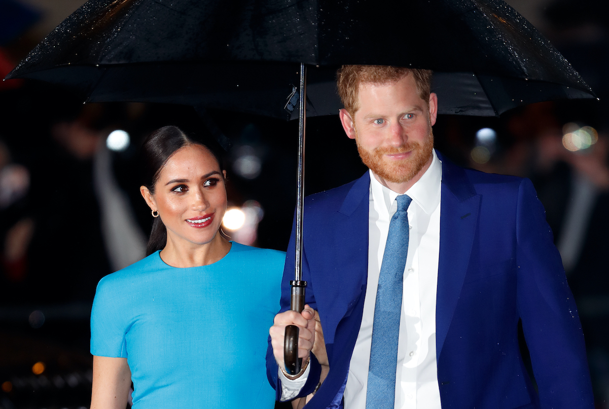 Prince Harry and Meghan Markle looking left and holding an umbrella