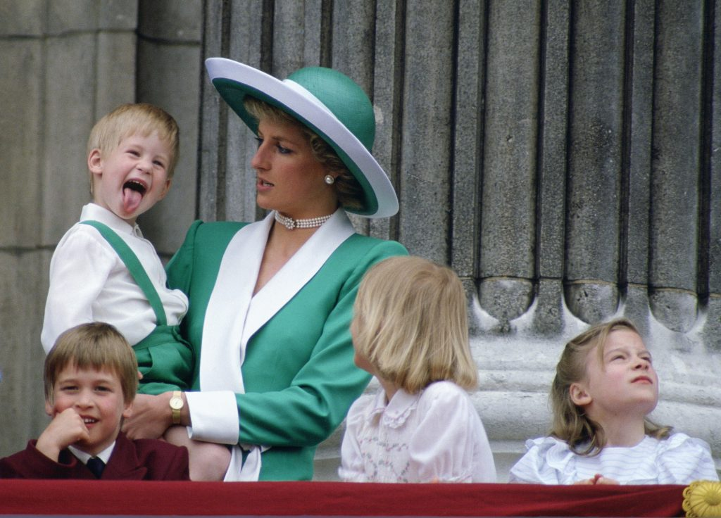 Princess Diana holding a young Prince Harry as he sticks out his tongue