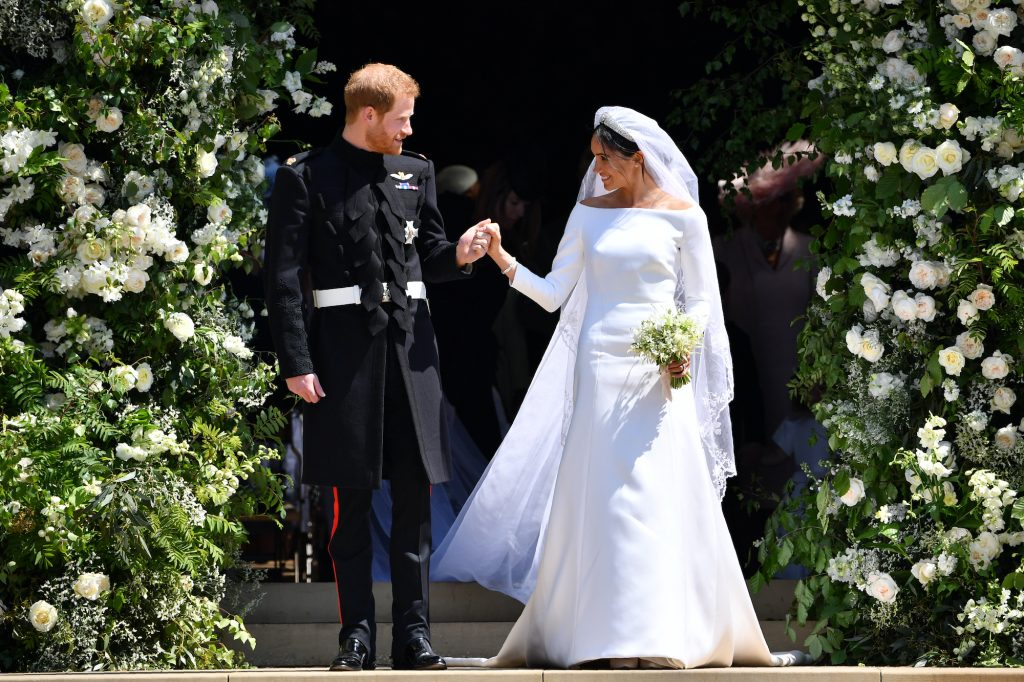 Prince Harry and Meghan Markle smiling at each other, walking out of the church on their wedding day