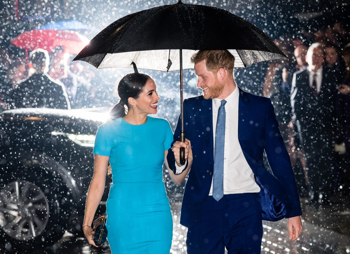 Prince Harry and Meghan Markle smiling at each other under and umbrella, walking in the rain