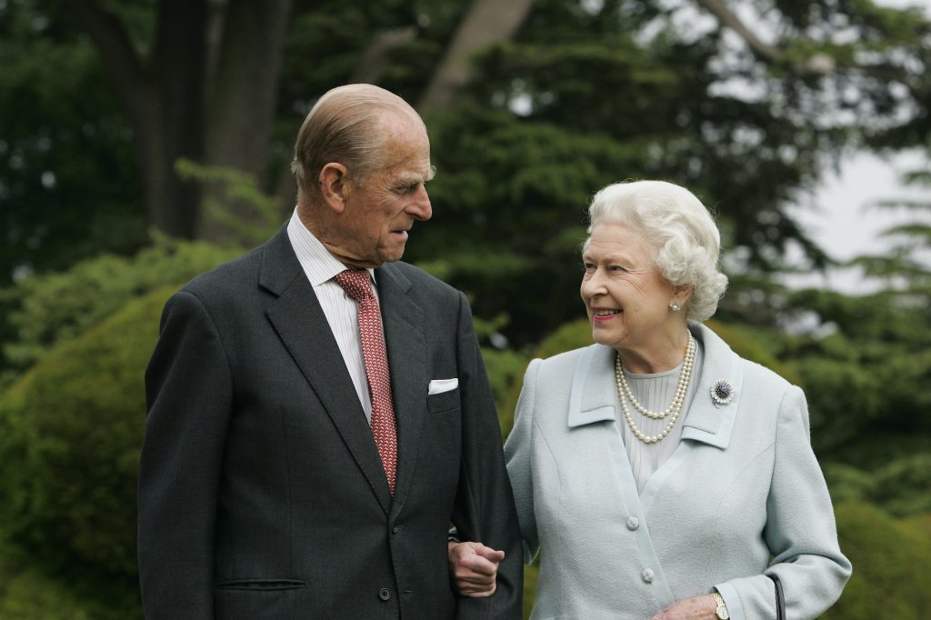 Prince Philip and Queen Elizabeth smiling at each other in front of blurred trees, 2007