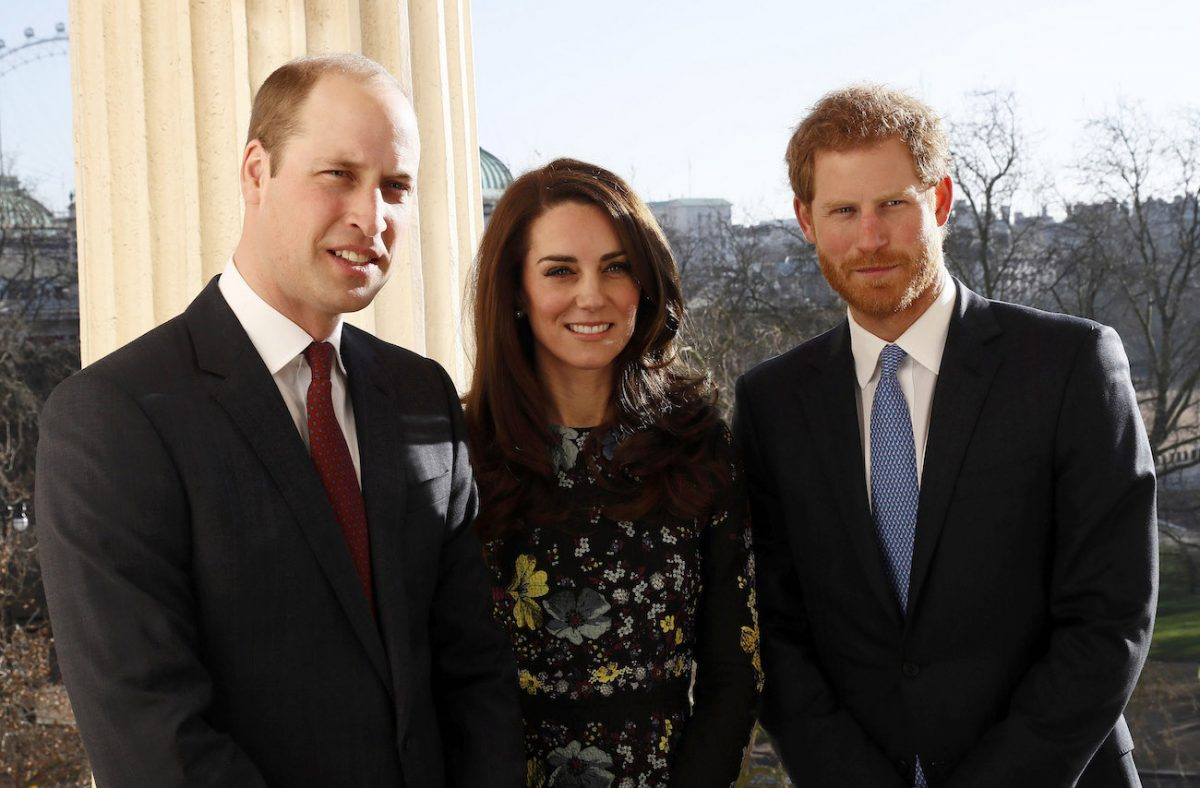 Prince William, Kate Middleton, and Prince Harry standing next to each other, smiling
