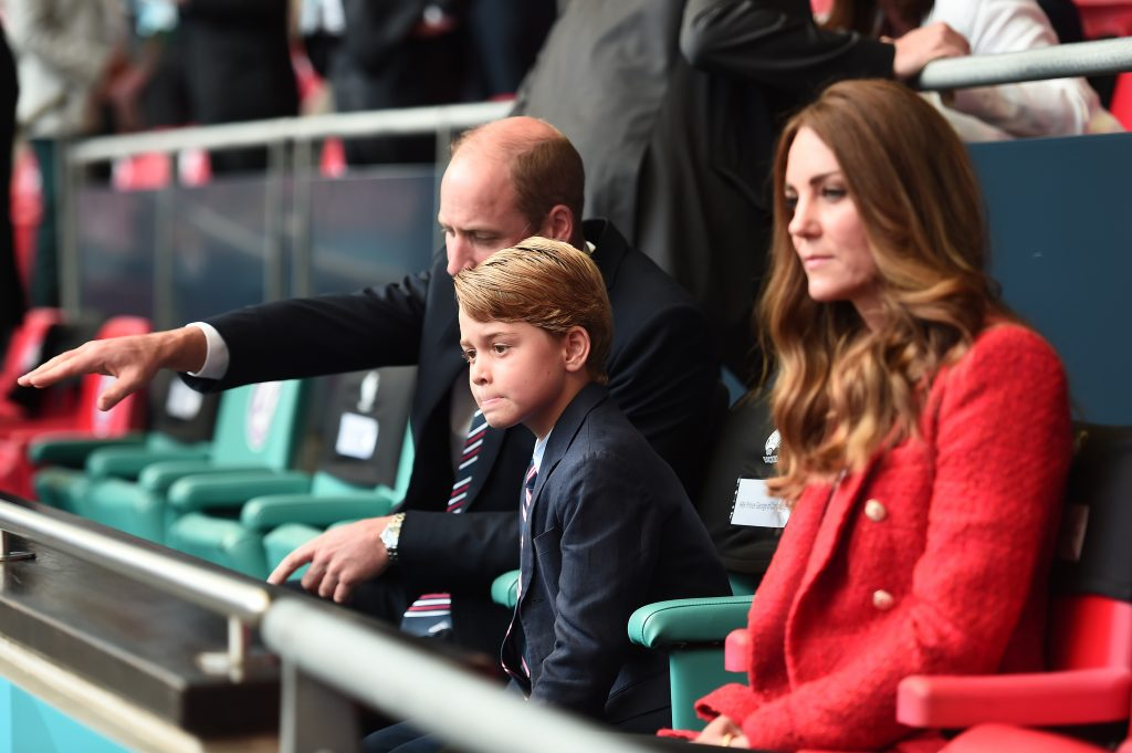 Prince William explaining something to Prince George as they sit in the stands with Kate Middleton at a football match
