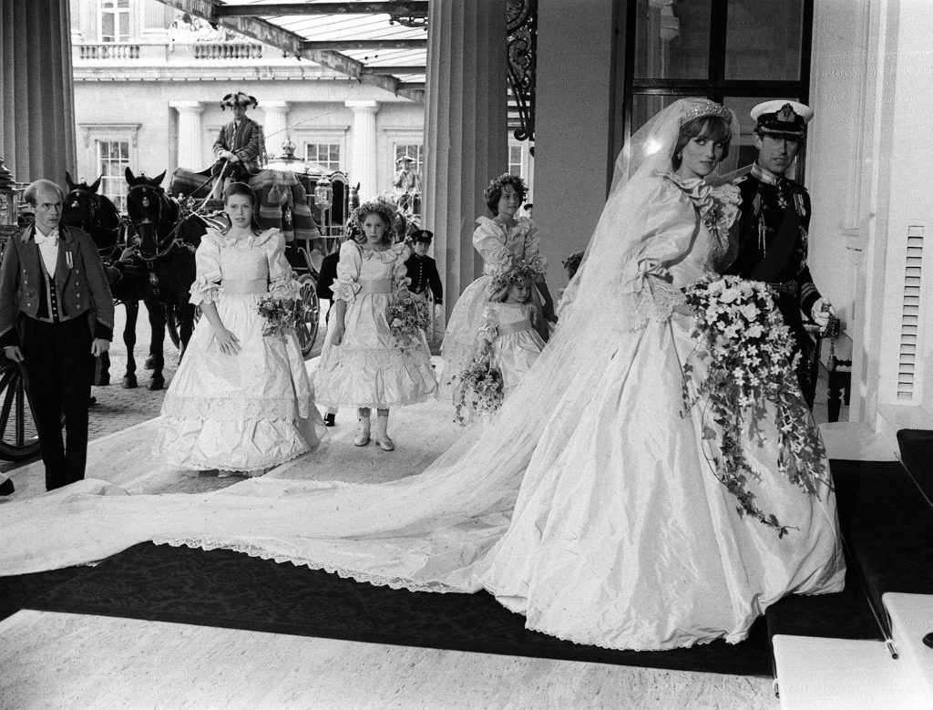 Princess Diana in one of the most iconic royal family looks, her 1981 wedding dress, walking with Prince Charles, in black and white. It's one of the royal family's best looks.